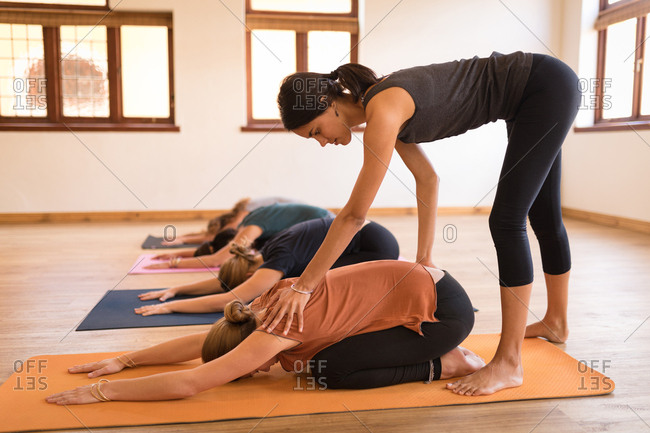 Female trainer assisting woman in yoga exercise at fitness club