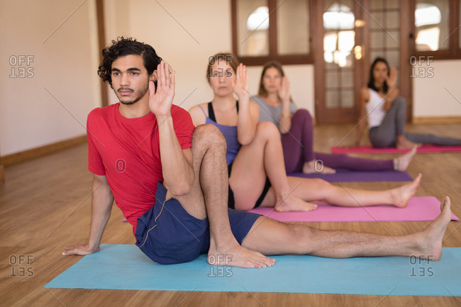 Group of people performing yoga exercise together in fitness club