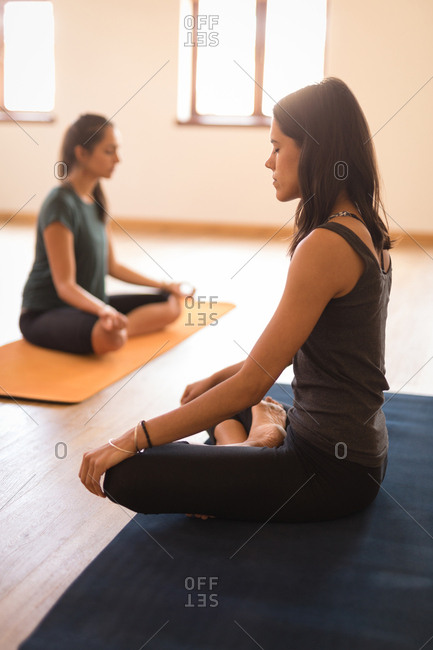 Young female trainer and woman meditating in fitness club