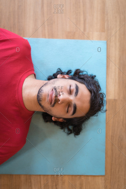 Young man meditating in fitness club