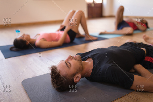 Group of people meditating together in fitness club