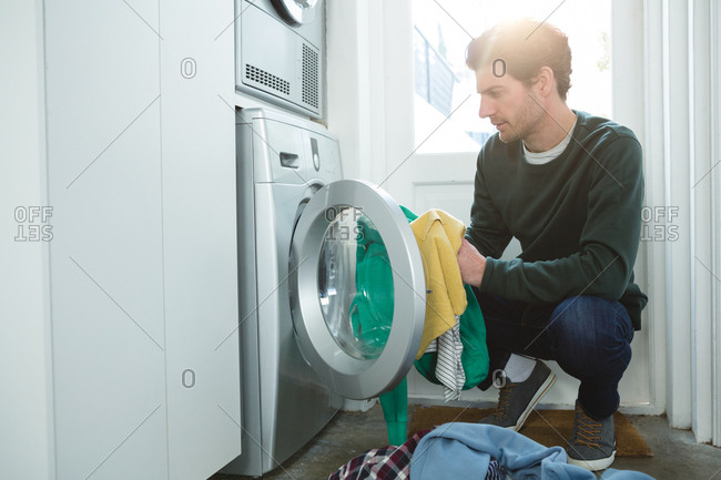 Man putting clothes in washing machine at home
