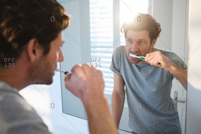 Man looking at mirror and brushing his teeth in bathroom at home