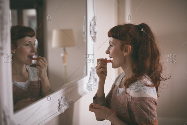 Woman applying lipstick in front of mirror at home