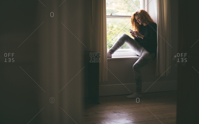 Woman using mobile phone while sitting on windowsill at home