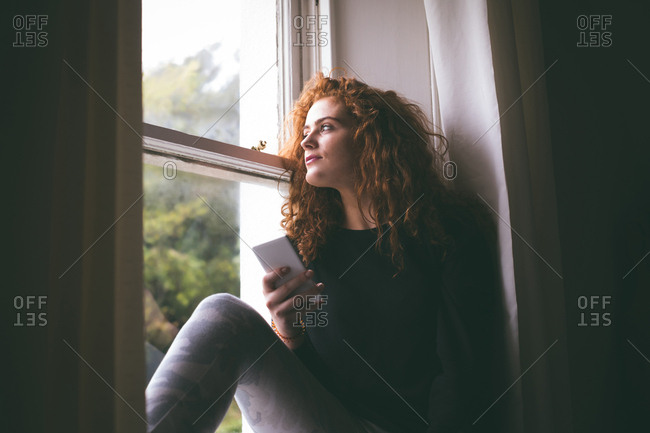 Thoughtful woman with mobile phone sitting on windowsill at home
