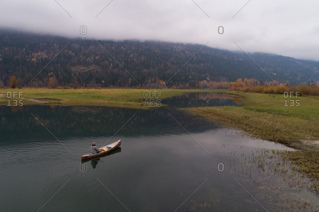 Male tourist travelling in canoe boat on a lake