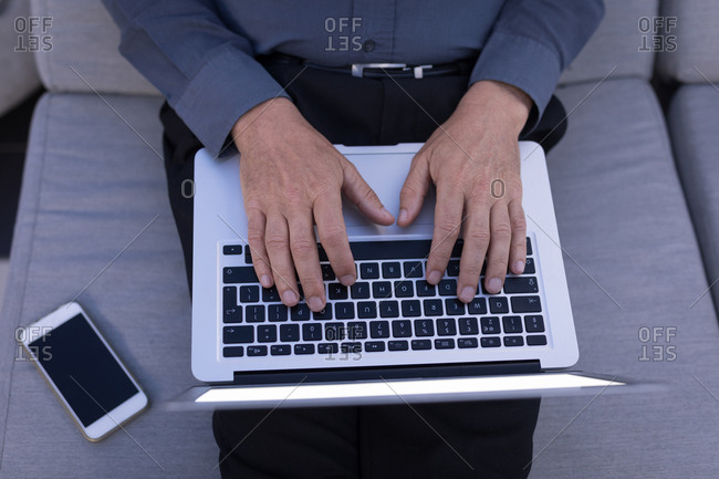 Mid section of businessman using a laptop