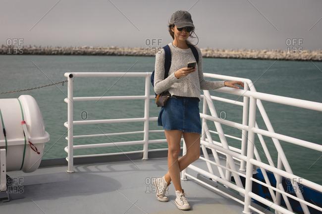 Beautiful woman using mobile phone on cruise ship