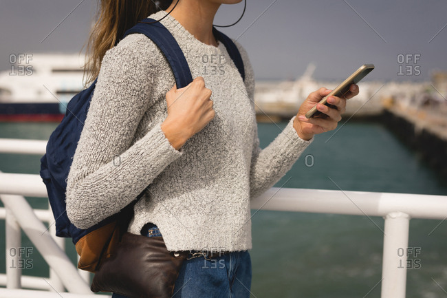 Mid section of woman using mobile phone on cruise ship
