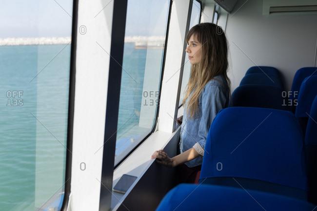 Beautiful woman looking through window while sailing in cruise ship