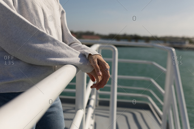 Mid section of woman standing near railings of cruise ship