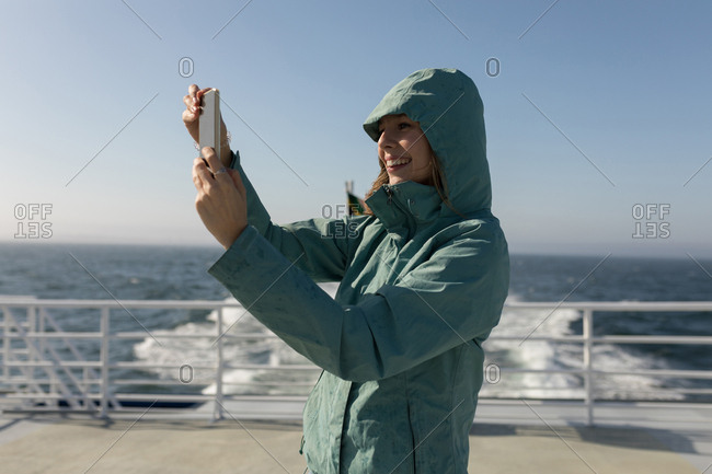 Woman taking selfie with mobile phone on cruise ship