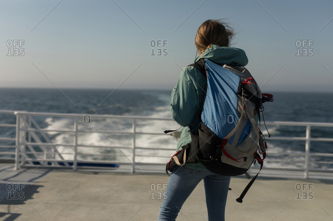 Rear view of woman with backpack standing on cruise ship