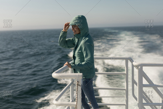 Woman in hoodie standing on cruise ship on a sunny day