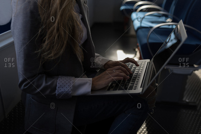 Mid section of woman using laptop in cruise ship