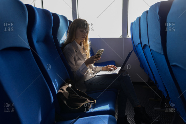 Woman checking mobile phone while using laptop in cruise ship