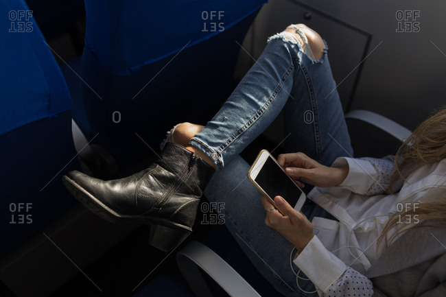 Low section of woman using mobile phone in cruise ship