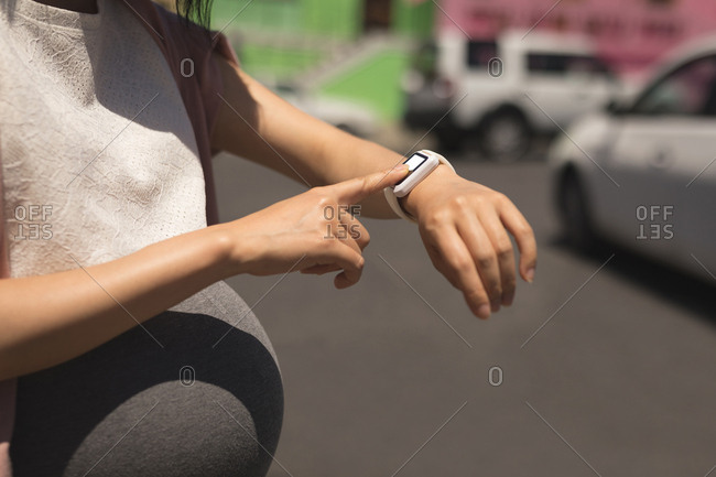 Pregnant woman using smartwatch on a sunny day