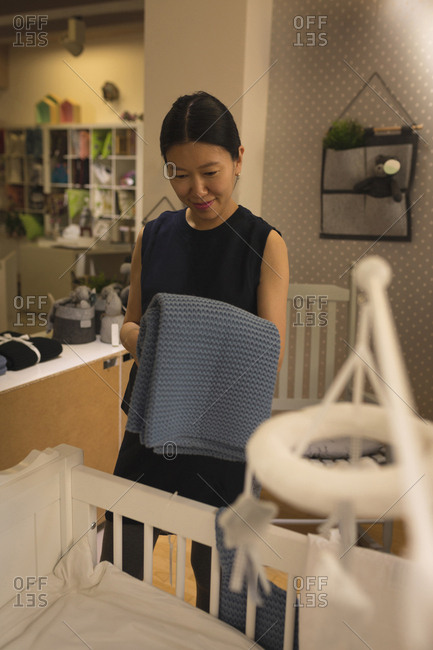 Happy pregnant woman looking at wooden cradle in store