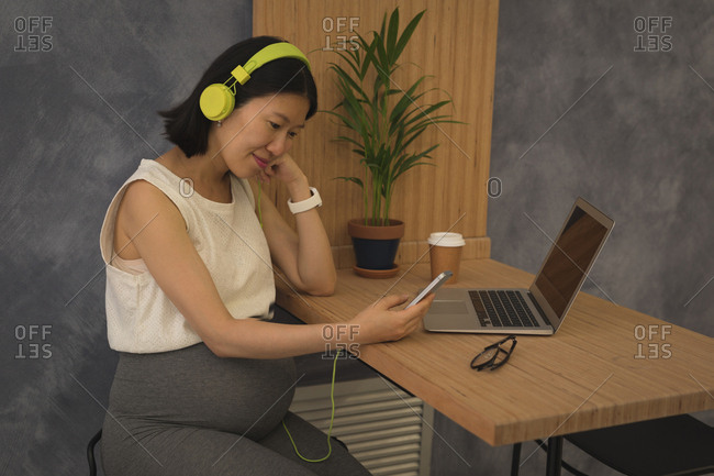 Pregnant businesswoman listening music on mobile phone at desk in office
