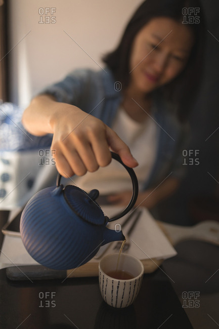 Pregnant woman pouring black coffee into cup at cafe