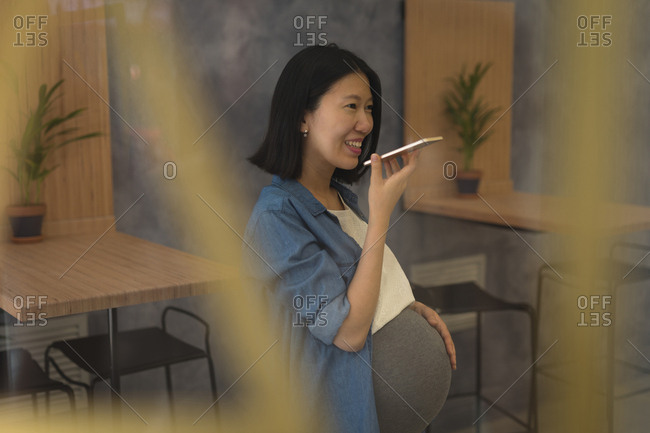 Pregnant businesswoman talking on mobile phone in office
