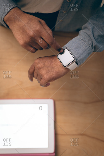 Overhead of executive using smartwatch in office