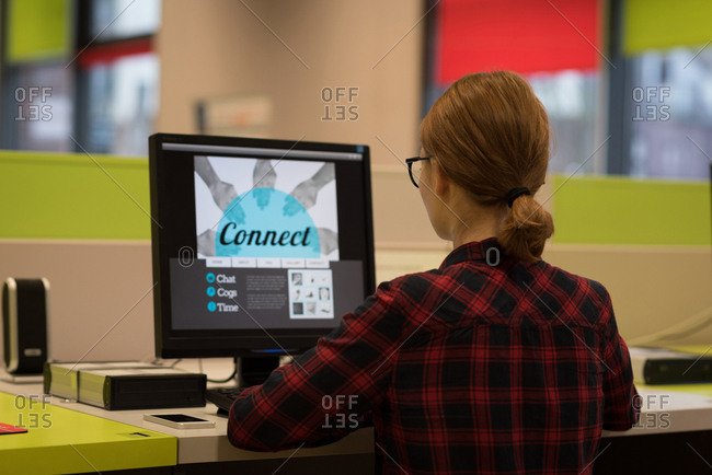 Young woman using a desktop pc in the library