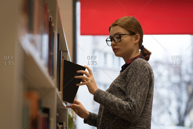 Young woman picking up a book from the bookshelf