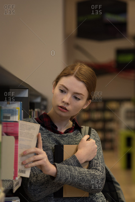 Young woman picking up a book from the bookshelf in library