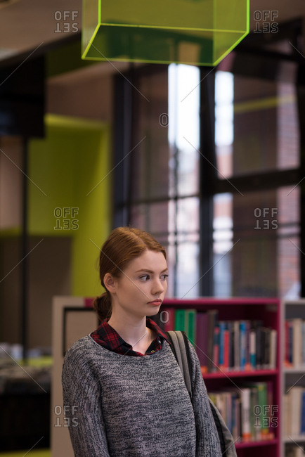 Thoughtful woman standing in the library