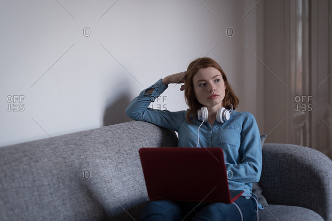 Thoughtful woman with laptop sitting on sofa in living room at home
