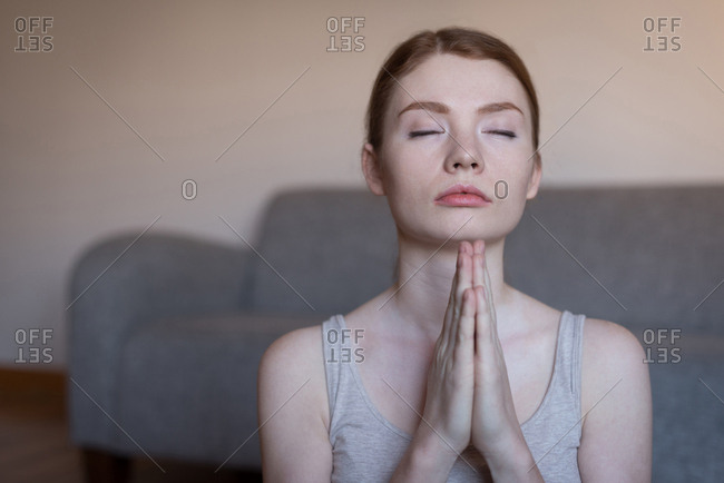 Young woman meditating with joined hands in living room