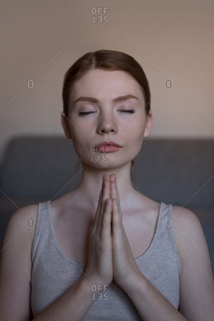 Close-up of young woman meditating with joined hands in living room