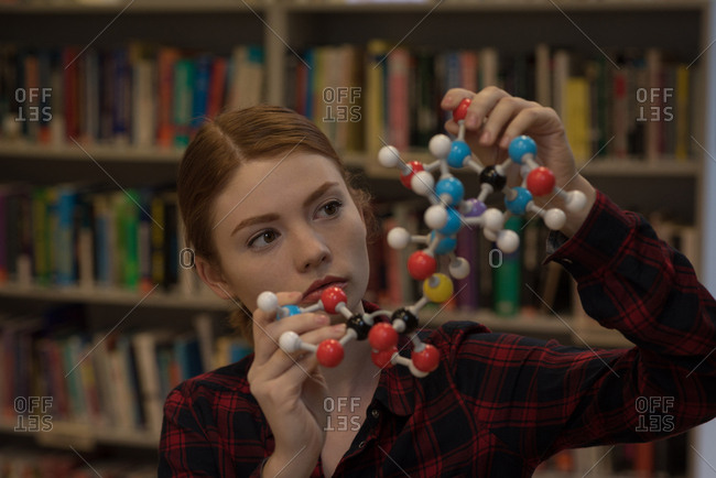Young woman analyzing a molecule model in the library