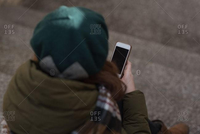 Woman in winter clothing using mobile phone on staircase