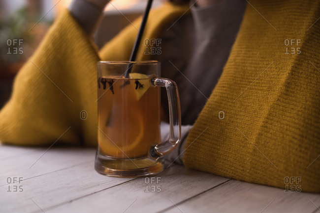 Mid section of woman having lemon juice with straw