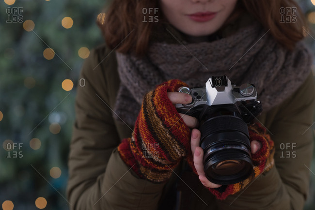 Mid section of woman in winter clothing holding vintage camera