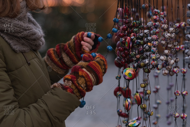 Mid section of woman in winter clothing holding christmas decoration