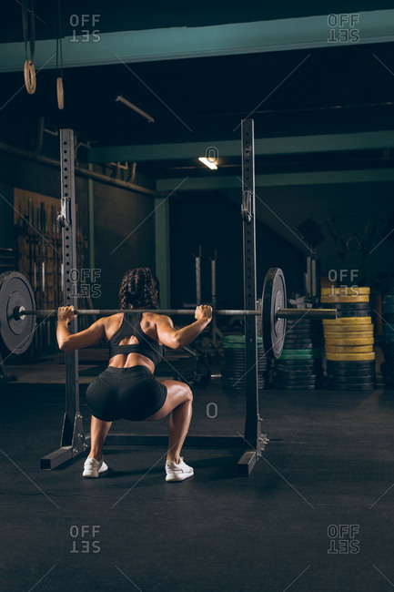 Rear view of fit woman lifting the barbell in the gym