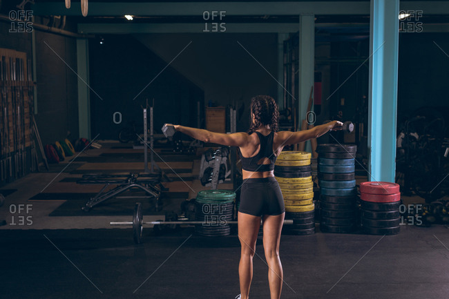 Rear view of fit woman exercising with dumbbells in the gym