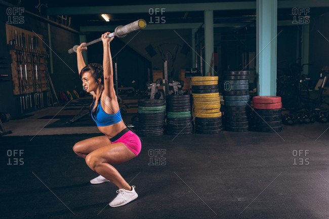 Fit woman lifting the barbell rod in the gym