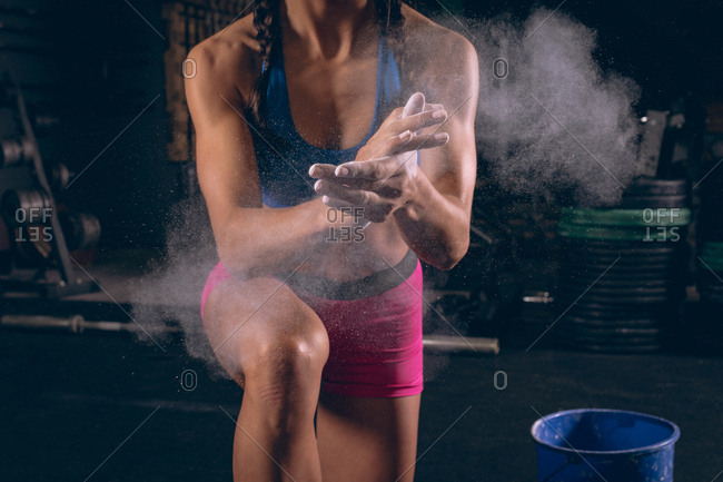 Mid section of fit woman dusting her hands with chalk powder in the gym
