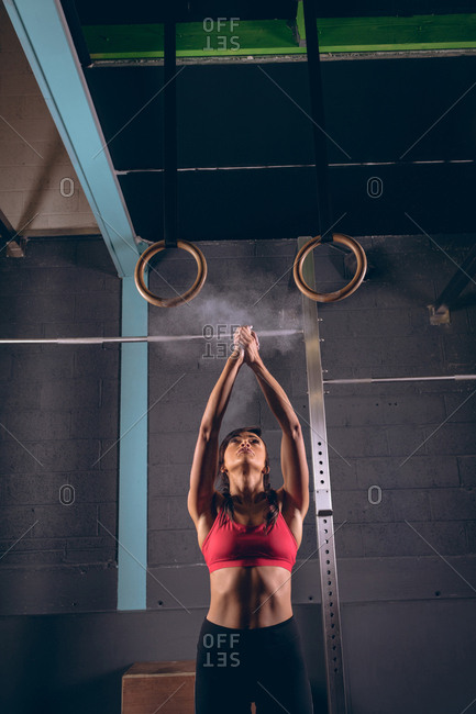 Fit woman dusting her hands with chalk powder in the gym