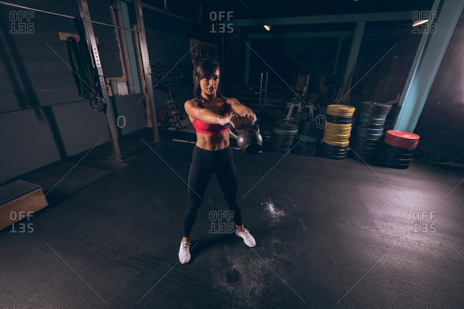 Fit woman exercising with kettlebell in the gym