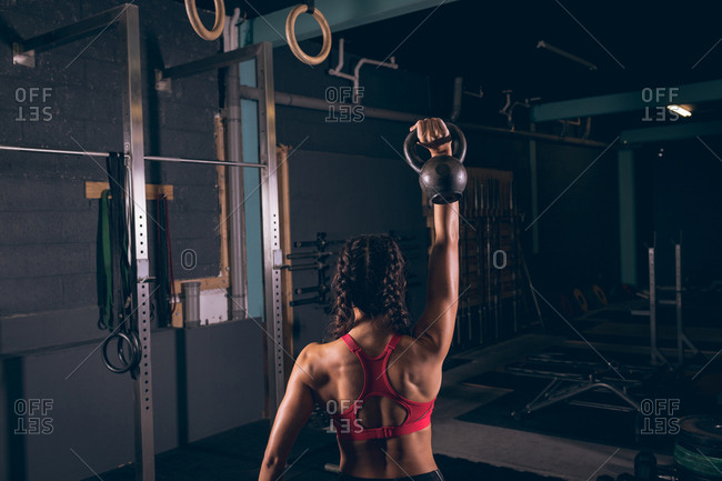 Rear view of fit woman exercising with kettlebell in the gym
