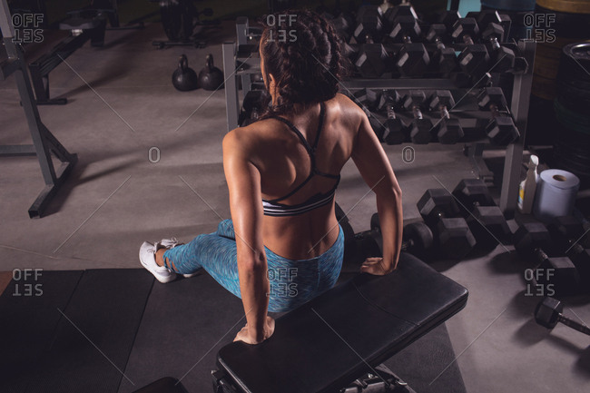 Fit woman exercising on gym bench in the gym