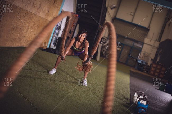 Fit woman doing battle rope exercise in the gym