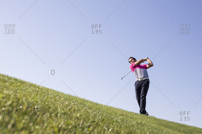 Golfer playing shot with an iron on fairway